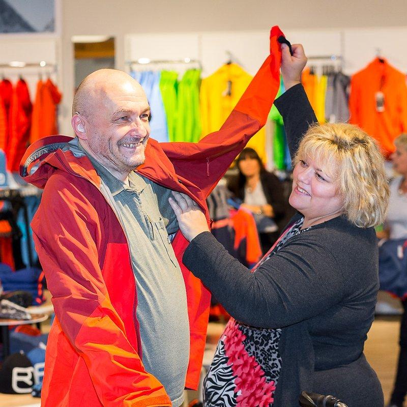 Assistentin unterstützt Assistenznehmer beim Anziehen