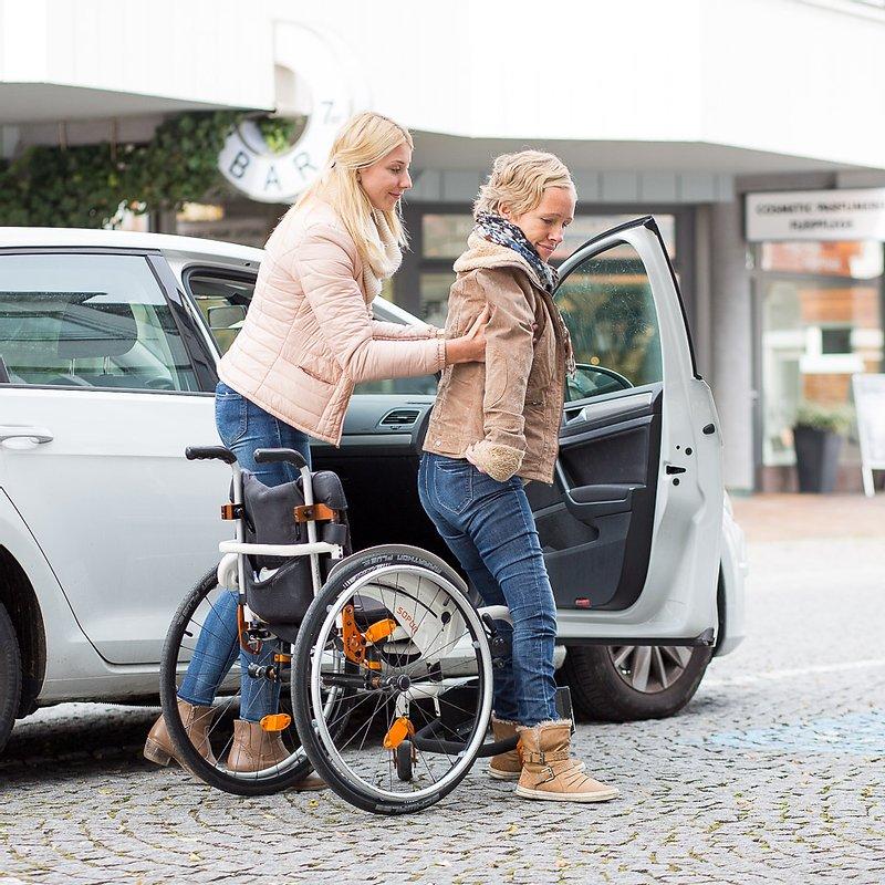 Assistentin unterstützt Assistenznehmer beim Einsteigen in ein Auto