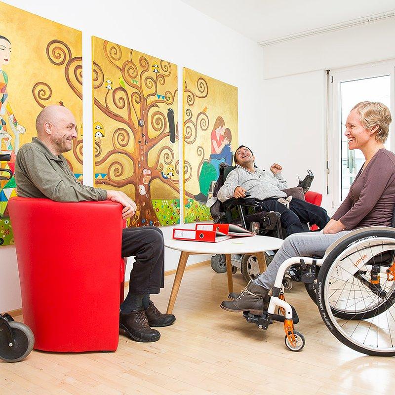 Teil des Teams der Servicestelle Persönliche Assistenz Vorarlberg sitzt gemeinsam um einen Tisch herum