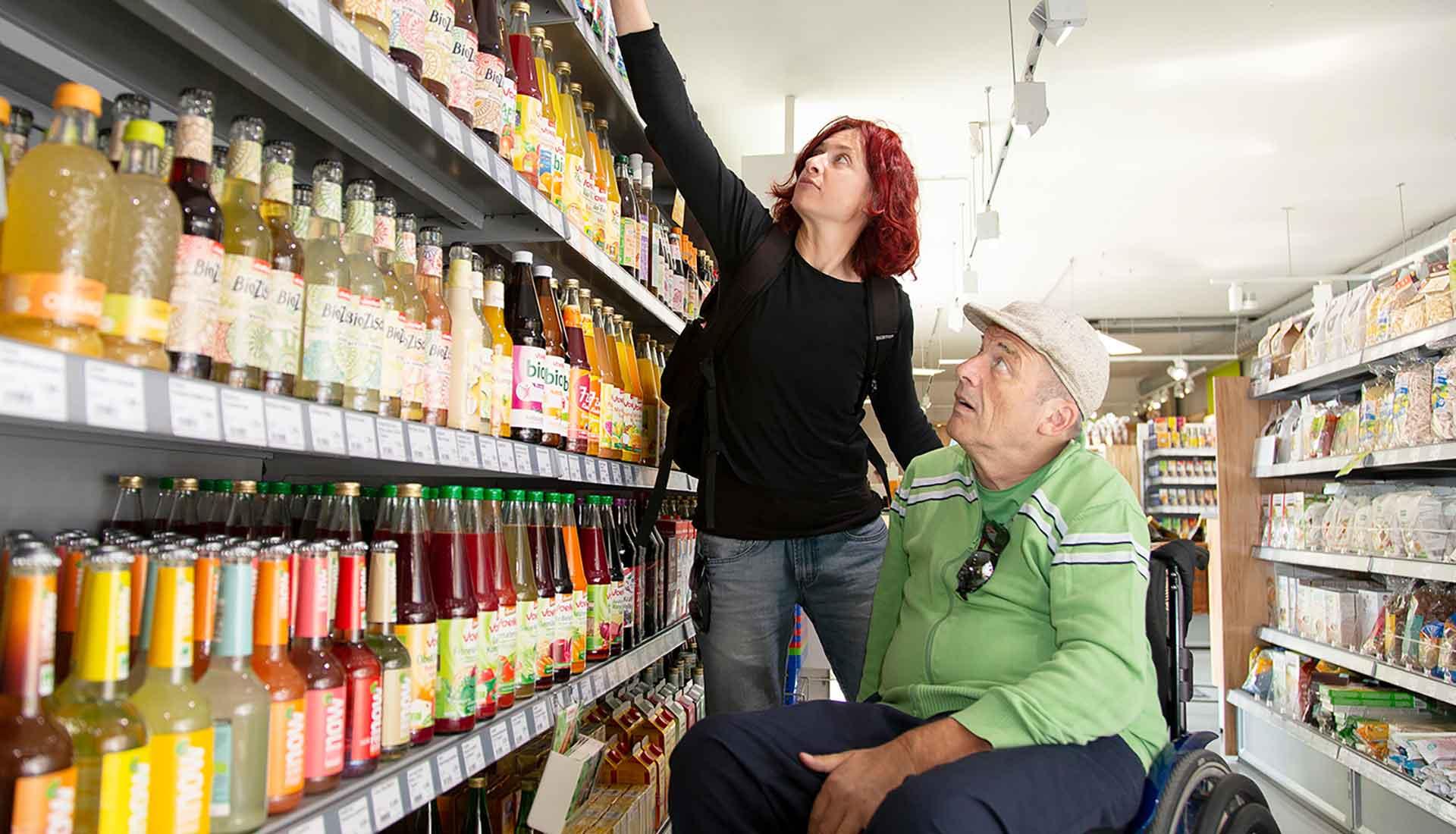 Assistenznehmerin wird von einer Assistentin beim Einkaufen unterstützt