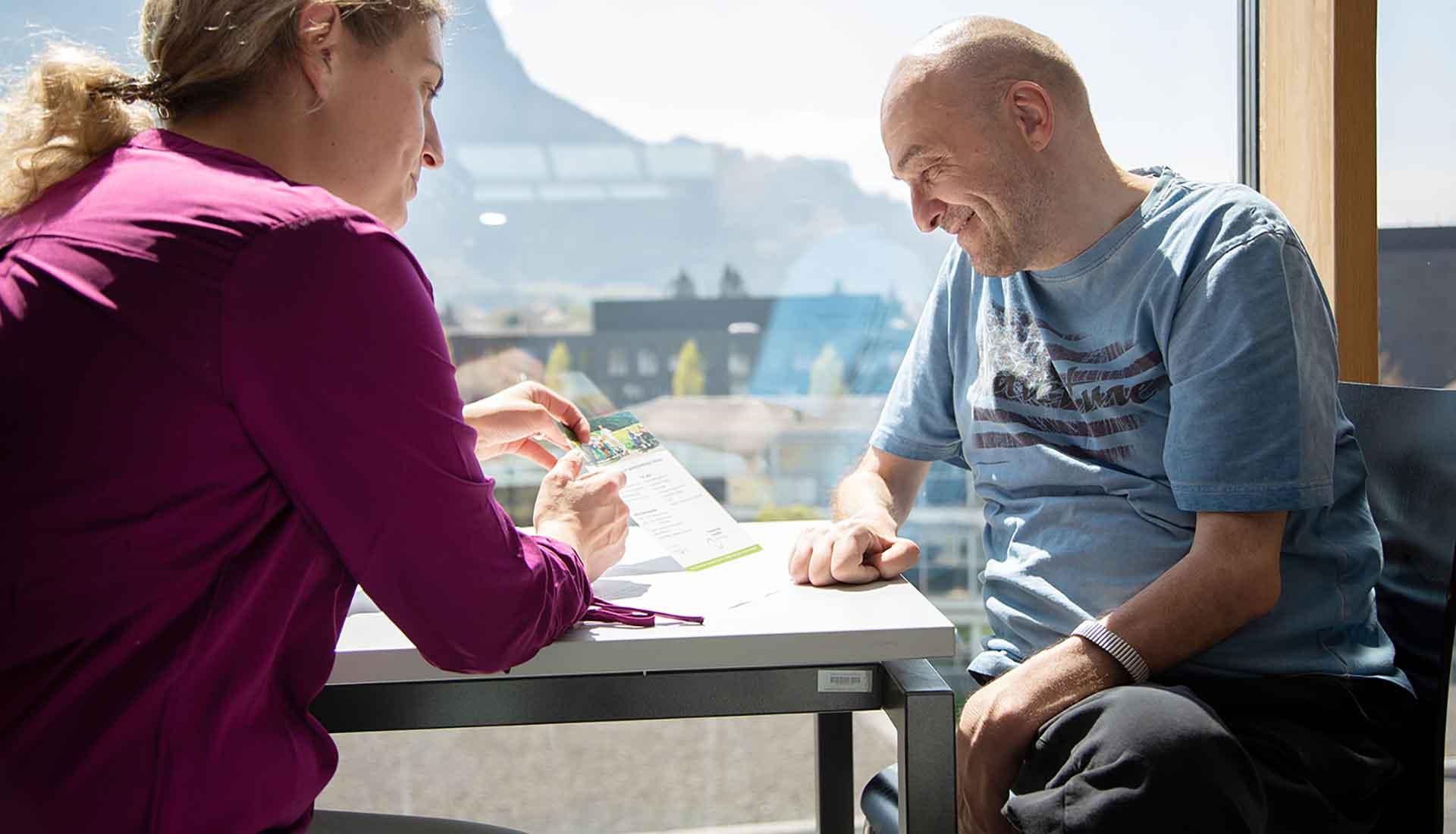 Assistenznehmer wird von einer Assistentin beim Lesen unterstützt