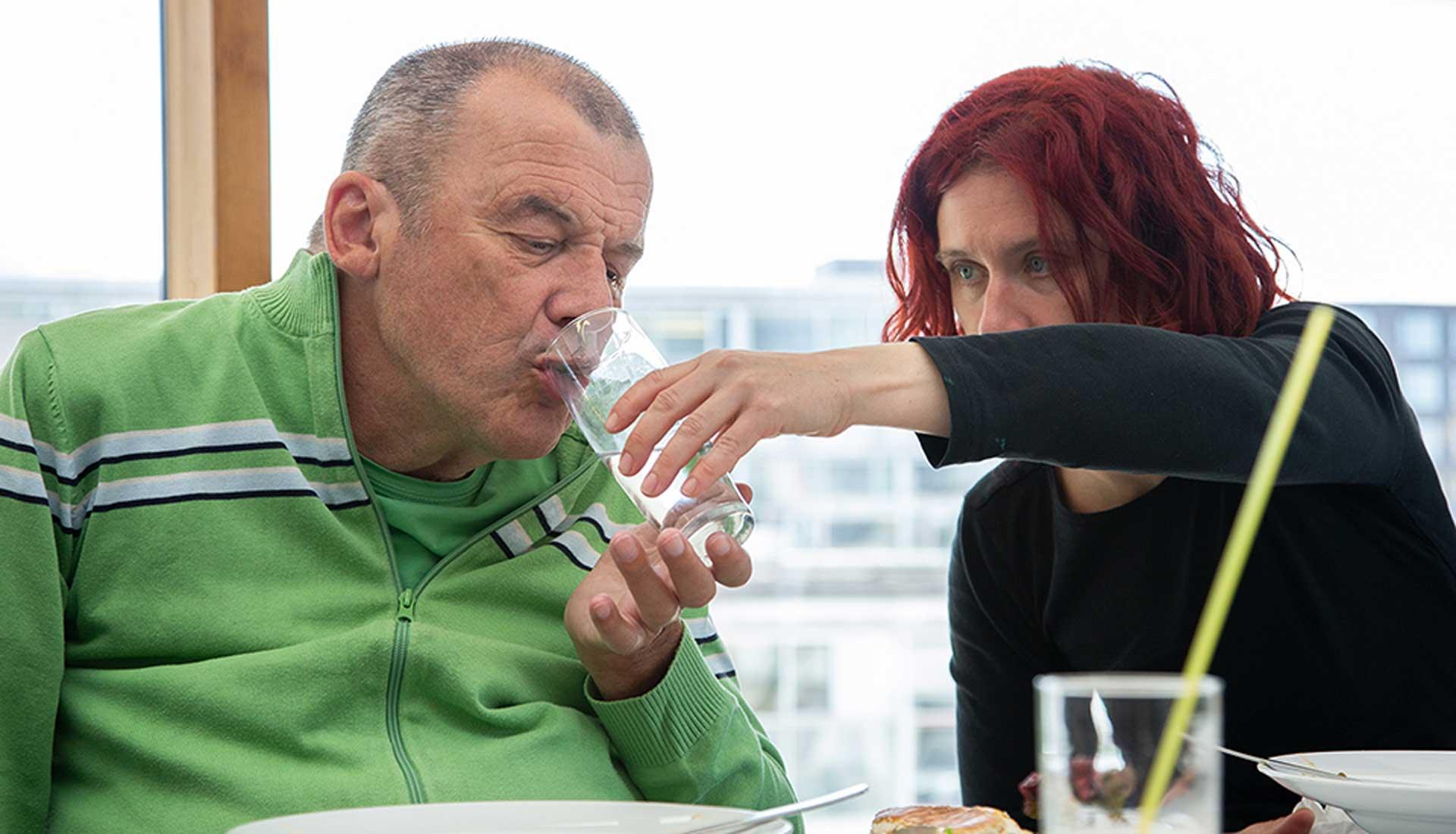 Assistenznehmer wird von einer Assistentin beim Trinken unterstützt