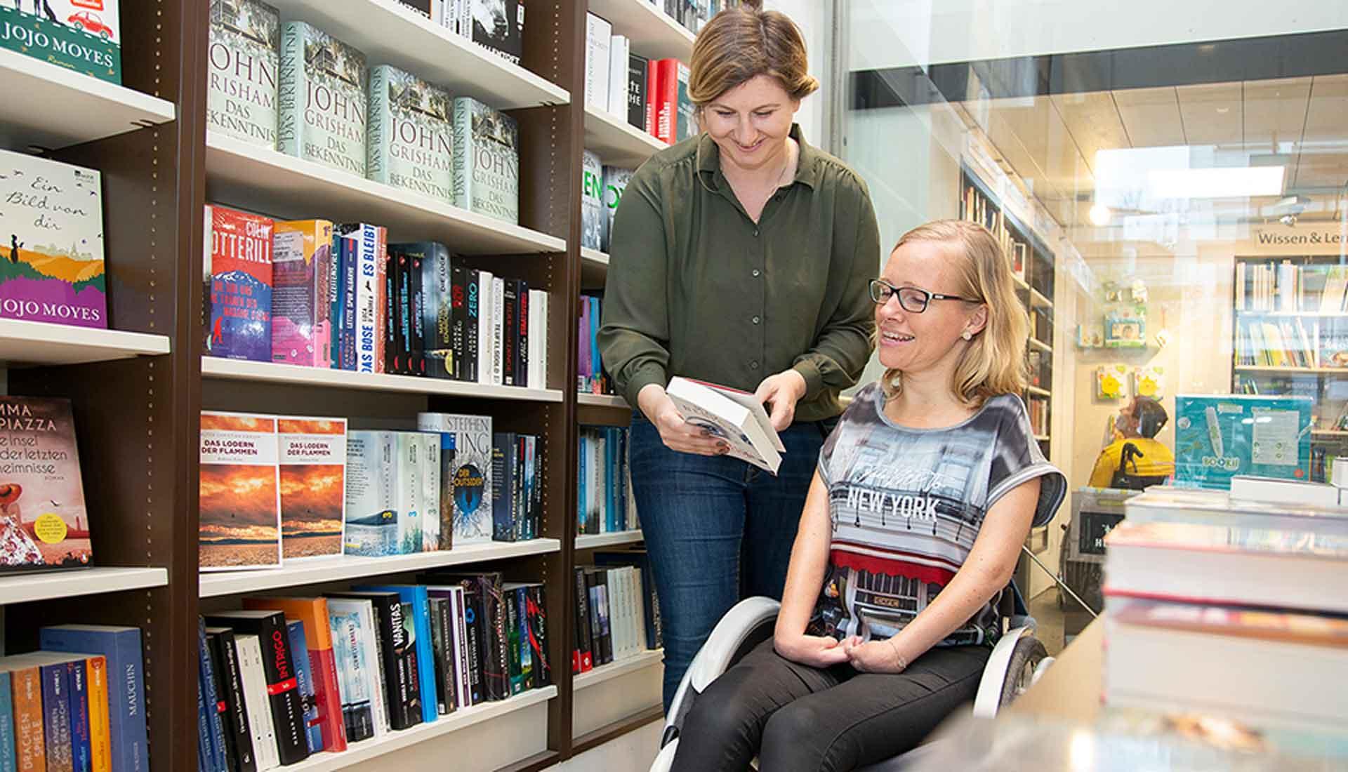 Assistenznehmerin wird von einer Assistentin in einer Bibliothek unterstützt