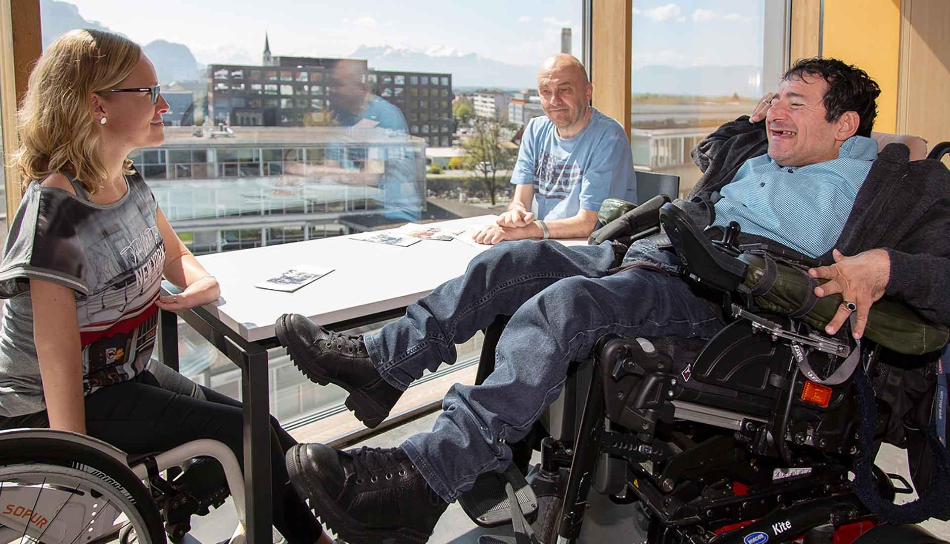 Teil des Teams der Servicestelle Persönliche Assistenz Vorarlberg sitzt gemeinsam an einem Tisch