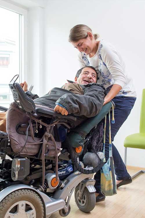 Assistenznehmer sitzt im Rollstuhl und wird von einer Assistentin unterstützt