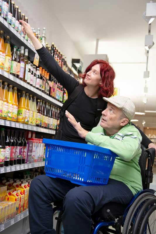 Ein Assistenznehmer im Rollstuhl und eine Assistentin beim gemeinsamen Einkaufen